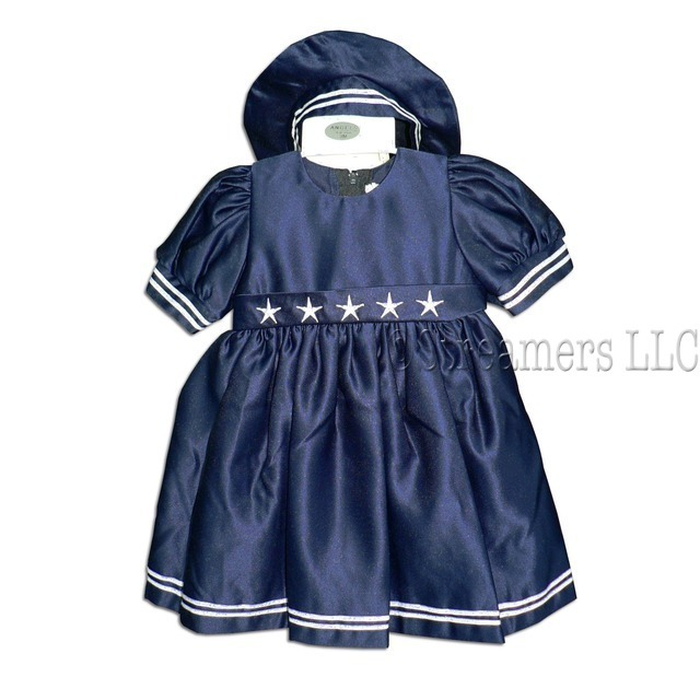 Adorable Baby Girl Sailor Dress in Navy Blue Satin with White Stars and Stripes, Lined Skirt, Panty and Matching Hat.  Ties in Back.  Comes in its own Garment Bag. Available in Sizes 3 and 6 months.