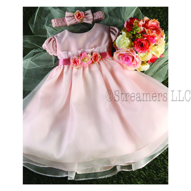Sweet baby girl dress with satin bodice, cap sleeves, floral and rhinestone embellishments that trim the ribbon ties.  Buttons at back.  Matching headband. Darling!  Available in Peach and White (Great for weddings and baptisms) in sizes 6/9, 12, 18 and 24 months. *Made in USA by Kid Collection