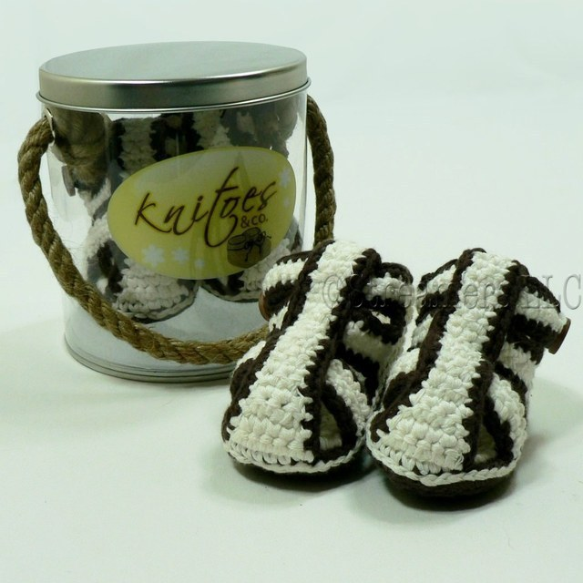 Baby Booties by Knitoes, Cool Knit Gladiator Sandals in Cream with Brown Stripes - Button Closure and Suede Sole.  Comes in a Display Pail with Rope Handle. Adorable!  Available in sizes Newborn, 3-6 Months and 6-12 Months (Individually boxed to protect pail)  Makes a Great Shower Gift!