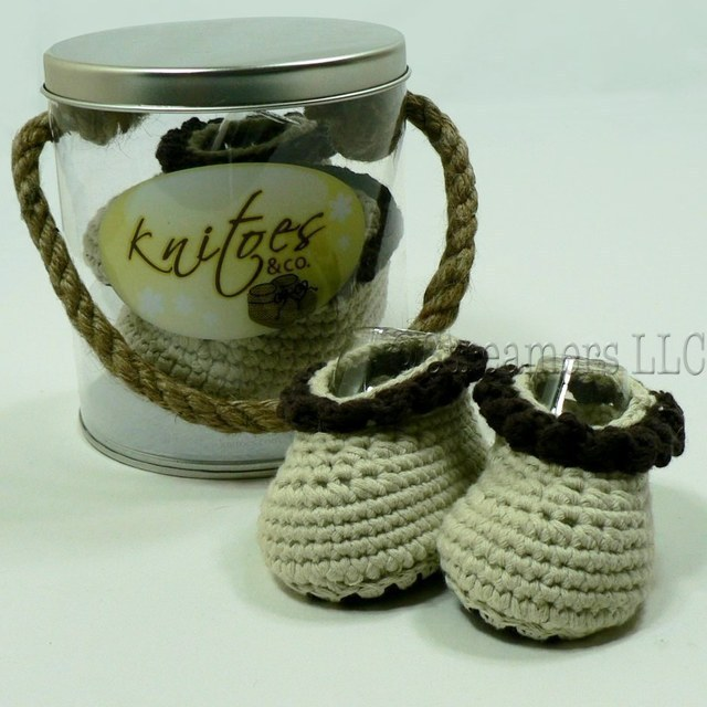 Baby Booties by Knitoes, Adorable Knit Baby Booties in Natural with Chocolate Brown Ruffle Trim and Soft Suede Soles.  Comes in a Display Pail with Rope Handle. Too Cute!  Available in sizes Newborn, 3-6 Months and 6-12 Months (Individually boxed to protect pail)  Makes a Great Shower Gift!