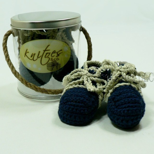 Baby Booties by Knitoes, Adorable Knit Lace-Up Booties in Navy with Natural Colored Laces and Soft Suede Soles.  Comes in a Display Pail with Rope Handle.   Available in sizes Newborn, 3-6 Months and 6-12 Months (Individually boxed to protect pail)  Makes a Great Shower Gift!