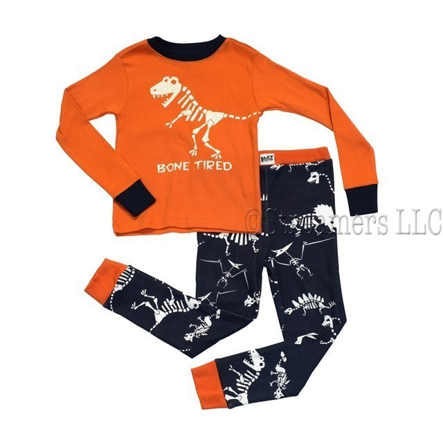 Great boys pajamas by Lazy One with a glow in the dark t-rex skeleton screen print on the top that reads Bone Tired and navy blue bottoms with various dinosaur skeletons. Cute! Available in sizes 6  *Wear snug fitting, not flame resistant.