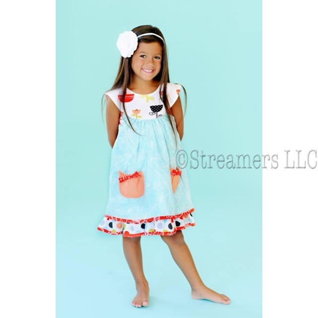Dresses by Jelly the Pug - Sweet Cotton Dress with Aqua Blue  Floral Print Top Layer with Bishop Style Cream Collar  over Multi-Color Dotted Dress with Orange Printed Trim.  Front Orange Polka Dot Pockets with Darker Orange Bows.  Large Orange Snap Buttons at Back.  Unique Colors.  Available in Sizes 6X.  See Larger Sizes in Tween Girl.  Style:  Opal Sailor