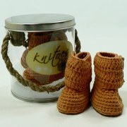 Baby Booties by Knitoes, Cozy Knit Baby Boots in Burnt Orange with Two Button Closure and Suede Soles.  Comes in a Display Pail with Rope Handle. Too Cute!  Available in sizes Newborn (Individually boxed to protect pail)  Makes a Great Shower Gift!
