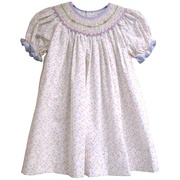 This dainty dress features a bishop smocked neckline with rosettes and white beads, blue plaid trim on neckline and sleeves, and a matching floral panty.  Available in sizes 12, 18 and 24 mos.